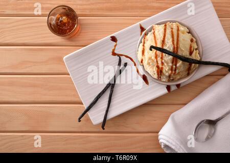 La vanille et crème glacée au caramel décoré avec des gousses de vanille sur une plaque sur une table en bois. Composition horizontale. Vue d'en haut. Banque D'Images