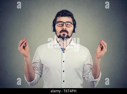 Portrait d'un bel homme dans les écouteurs avec les yeux fermés à écouter de la musique et la méditation Banque D'Images