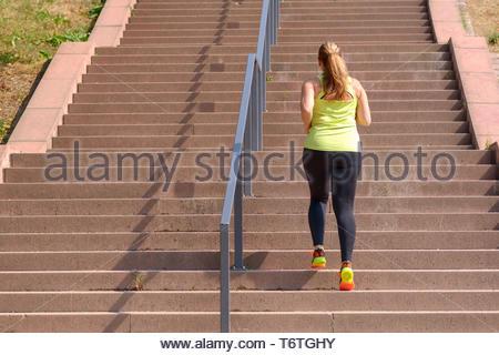 Femme d'exécution au moment de monter les escaliers pendant l'entraînement Banque D'Images