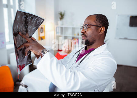 Médecin barbu looking at x-ray de petite fille blonde