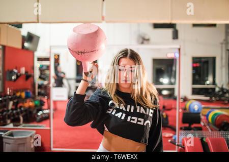 Fit woman l'entraînement avec kettlebell rose dans la salle de sport