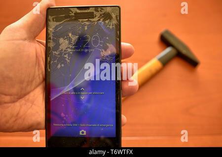 Gros plan sur un écran de smartphone avec un écran cassé et un millier de fissures. Un marteau à l'arrière-plan. L'affichage a été activée pour tester son ope Banque D'Images