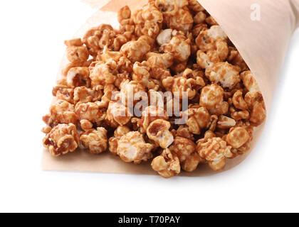 Délicieux avec du pop-corn caramel enveloppés de papier sur fond blanc Banque D'Images