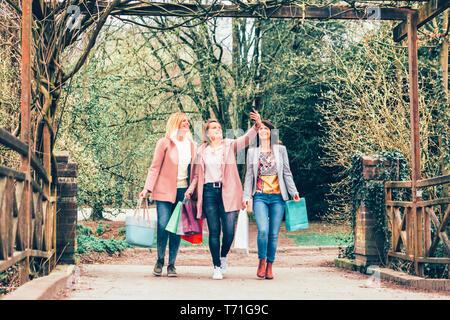 Trois jeunes femmes dans un parc de sourire et de prendre soin les sacs qu'ils prennent un tout en selfies sur la marche - solidarité, temps libre, l'amitié et la consommation Banque D'Images