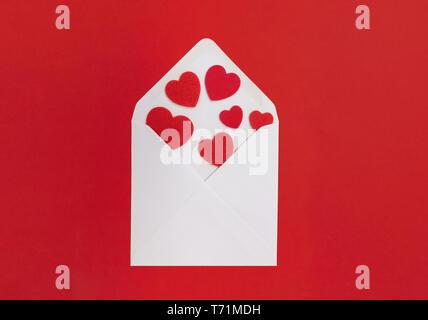 Concept de lettre d'amour. Enveloppe blanche avec des coeurs ne se répande au-dehors, avec un fond rouge. Banque D'Images