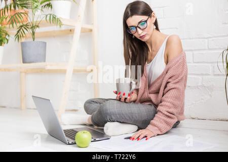 Jeune femme assise sur le sol dans un appartement scandinave intérieur avec un ordinateur portable, d'étudier le droit, freelance girl at work, étudiant l'apprentissage à distance