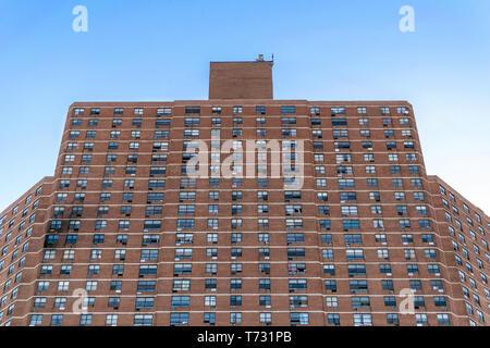 Grand immeuble complexe dans Harlem, avec des dégâts de feu visible sur le côté gauche, New York City, NY, USA Banque D'Images