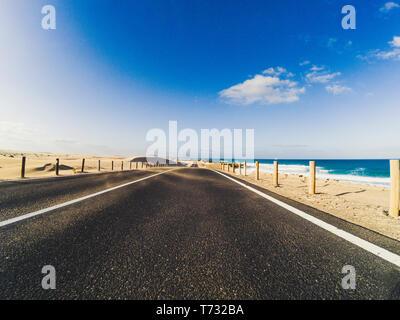 Long chemin road pour le transport en voiture concept avec désert et plage sur le côté - l'eau de mer et le bleu clair beau ciel en arrière-plan - motion
