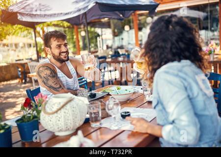 Smiling couple aimant assis dans un restaurant bénéficiant dans la bière et la conversation