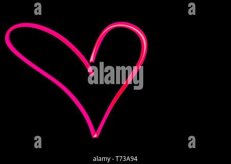 Vue horizontale d'un coeur rose contours light painting en noir ciel nocturne