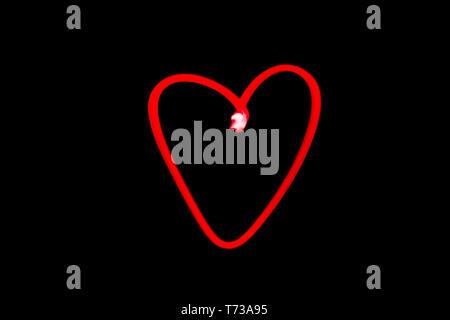 Vue horizontale d'un cœur rouge contours light painting dans Black Night Sky