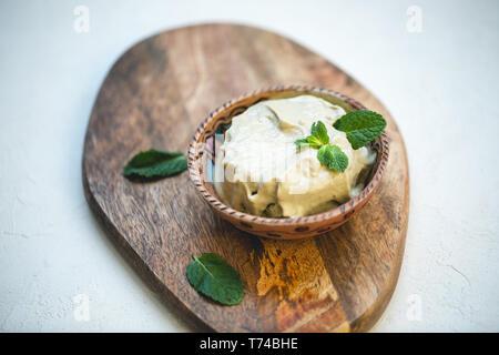 Vegan vert avocat fait maison ou glace gelato pistache avec les feuilles de menthe dans un bol sur une planche de bois. L'espace de copie, selective focus. Banque D'Images