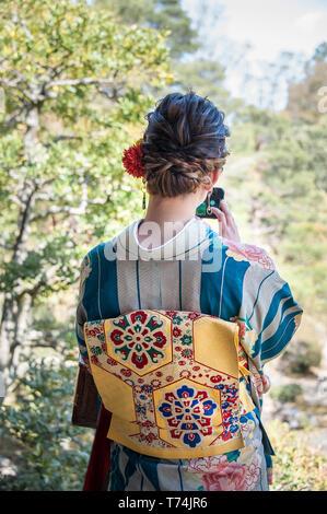 Vue arrière du girl wearing Kimono magnifique pour prendre des photos avec votre téléphone mobile en un jardin Banque D'Images