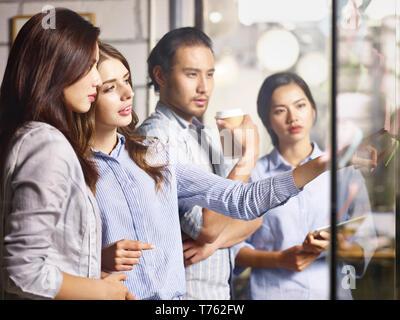 Équipe de jeunes entrepreneurs asiatique et caucasienne discuter affaires à l'aide de ruban adhésif notes in office. Banque D'Images