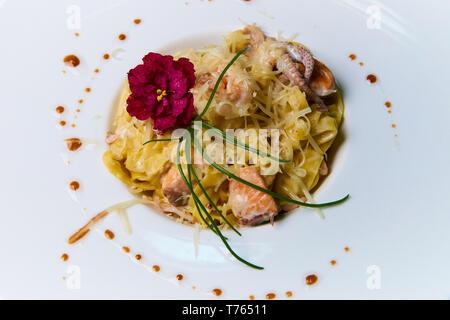 Plat de fruits de mer avec sauce et fleur sur fond blanc. Banque D'Images