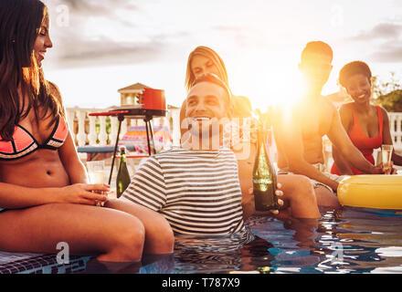 Groupe d'amis heureux de faire un pool party drinking champagne au coucher du soleil en vacances - Les jeunes gens rire et s'amuser avec vin mousseux Banque D'Images