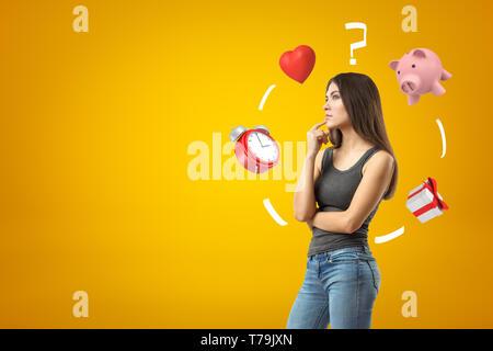 Jeune fille brune portant des jeans occasionnels et t-shirt, pensées avec coeur rouge, le point d'interrogation, tirelire et boîte-cadeau sur jaune Banque D'Images