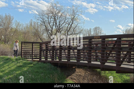 Aurora, Colorado - 3 mai 2019: Beau paysage avec passerelle pour piétons dans le petit parc de quartier, femme de la région de venir à la passerelle. Banque D'Images