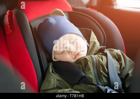 Close Up portrait of cute baby garçon endormi dans un siège de voiture. Sécurité enfant voyageant sur la route. Moyen sûr de voyager attaché leur ceinture de sécurité dans un véhicule Banque D'Images