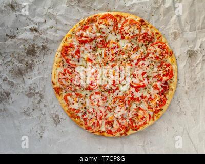 Délicieuse pizza Margherita ou Marguerite de fromage mozzarella, tomates et basilic sur le dessus de la pâte fine vue sur le fond de papier huilé froissé. Banque D'Images