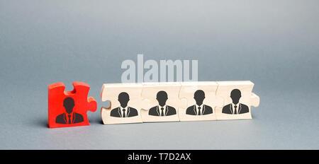 Puzzles en bois avec l'image des travailleurs. Le concept de la gestion du personnel dans l'entreprise. Rejetant un employés d'une équipe. Rétrogradation. Mauvais worke Banque D'Images
