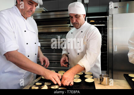 Deux employés de sexe masculin travaillant en cas de pâtisserie traditionnelle pour les Pasteis de nata tartelettes portugaises à l'intérieur d'une pastelaria dans Alfama Lisbon KATHY DEWITT Banque D'Images