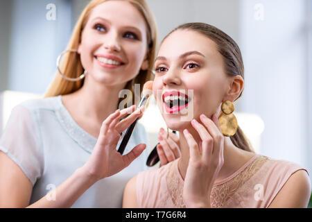 Agréable sensation de joie femme enthousiaste à son maquillage Banque D'Images