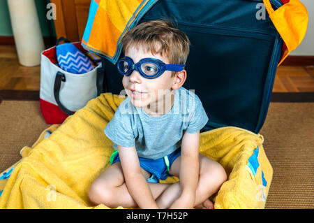 Funny boy smiling sitting dans une valise prête à partir en vacances Banque D'Images