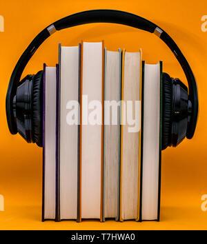 Livres audio concept. Mettre les écouteurs sur livre sur fond orange. Banque D'Images