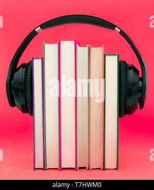 Livres audio concept. Mettre les écouteurs sur livre sur fond violet rose. Banque D'Images