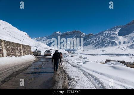 Entraînement d'hiver à belle & lonely planet de la neige dans la vallée de Spiti, Himachal Pradesh, Inde - homme marchant à travers des routes glissantes glacées Banque D'Images