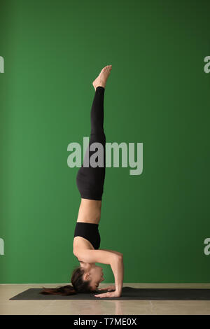 Young woman practicing yoga on près de mur de couleur Banque D'Images