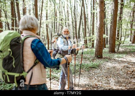 Beau couple randonnées avec sacs à dos et bâtons de trekking dans la forêt. Concept de vie active à la retraite