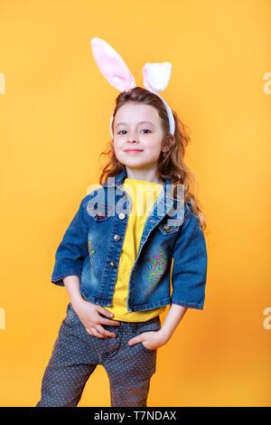 Cute little girl wearing Bunny Ears le jour de Pâques sur fond orange Banque D'Images