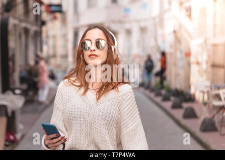 Belle jeune fille à la mode attrayant en cavalier et jeans avec un casque lunettes smartphone et écouter de la musique tout en marchant dans la foule