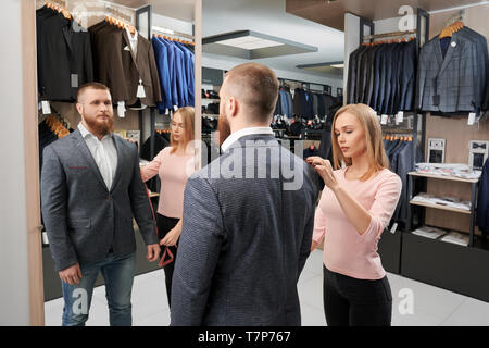 Vue de l'arrière de l'homme sérieux cherche client sur nouvelle veste et à la jolie assistante miroir tout en mesurant la longueur du manchon en magasin de vêtements. Concept de style et la mise en place. Banque D'Images