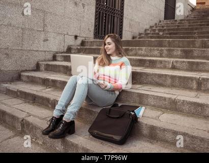 Teen vogue belle fille étudiant ou jeune college woman working on laptop sur l'Internet, blogs, chat ou sur les mesures en milieu urbain en arrière-plan sur