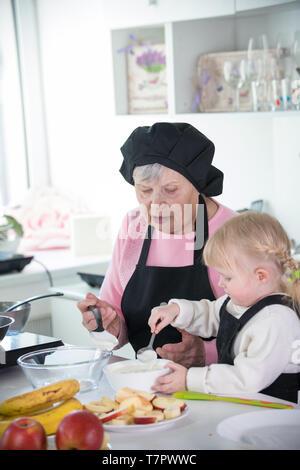 Dans la cuisine familiale. Une petite fille et sa grand-mère qui sert des crêpes avec de la crème Banque D'Images