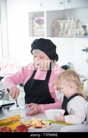 Une petite fille et sa grand-mère qui sert des crêpes avec de la crème Banque D'Images