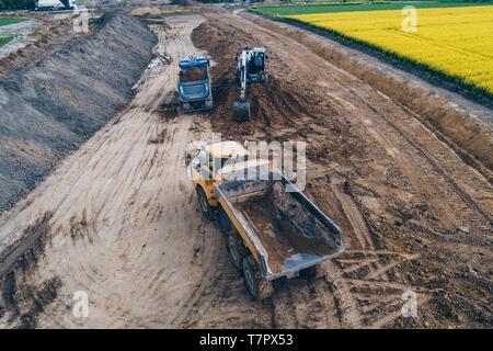 Drone aérien vue sur le chargement de l'excavateur sur camion benne de sable. La construction de routes Banque D'Images