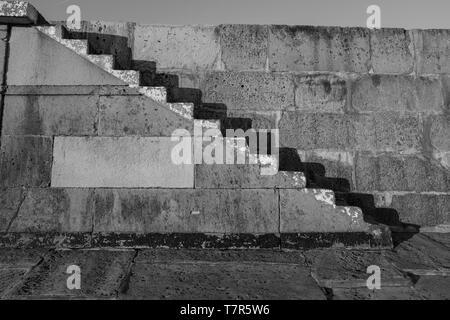 Vieux escaliers de pierre sur la Lyme Regis Cobb, tourné en noir et blanc avec des ombres contre le mur de pierre. Banque D'Images