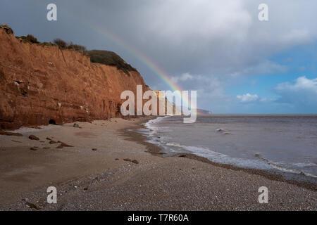 Un arc-en-ciel touche le sol sur une plage de Sidmouth dans le Devon, en Angleterre, avec les falaises rouges et ciel bleu