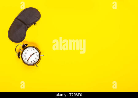 Concept de sommeil montrant un masque d'oeil et réveil sur un arrière-plan Banque D'Images