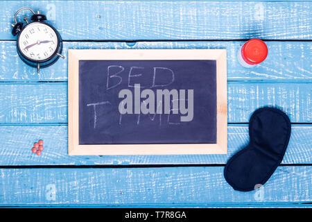 Concept de sommeil montrant un réveil, un somnifère, un masque d'oeil et un tableau noir lecture l'heure du coucher sur un fond bleu patiné Banque D'Images
