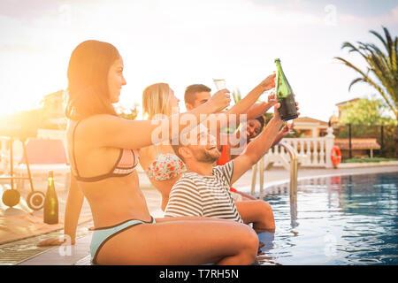 Groupe d'amis heureux de faire un pool party au coucher du soleil - Les jeunes gens rire et s'amuser drinking champagne at barbecue poolparty en locations Banque D'Images