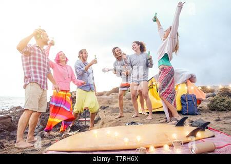 Happy friends s'amusant à jouer de la guitare et danser sur la plage - groupe de jeunes faisant partie de boire des bières en camping avec tente Banque D'Images