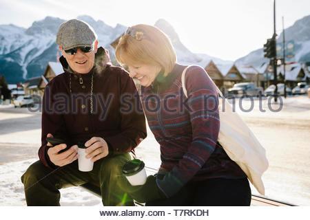 Couple using smart phone et de boire du café sur banc de neige, soleil Banque D'Images