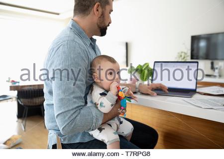 Père avec baby son travail à domicile, à l'aide d'ordinateur portable dans la cuisine Banque D'Images