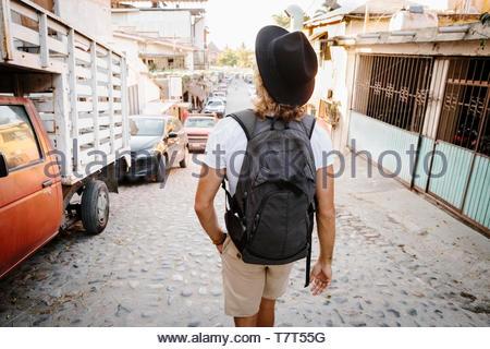 Jeune homme touriste avec sac à dos marche sur rue pavée, Mexique Banque D'Images