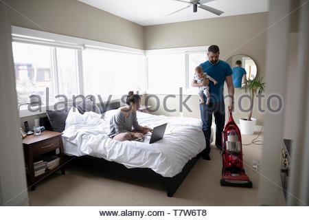 Femme travaillant à la maison, à l'aide de l'ordinateur portable sur lit tandis que mari détient et aspirateurs bébé Banque D'Images